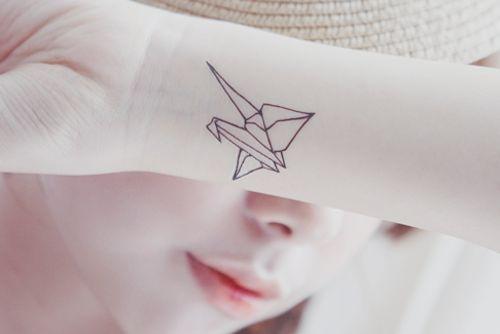 Joli et simple cygne en tatouage contour sur le poignet https://tattoo.egrafla.fr/2016/01/17/modele-tatouage-origami-animaux-avion-bateau/