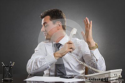 Annoyed indifferent businessman having an uninteresting phone conversation while holding receiver facing the other hand palm in a talk-to-the-hand gesture.