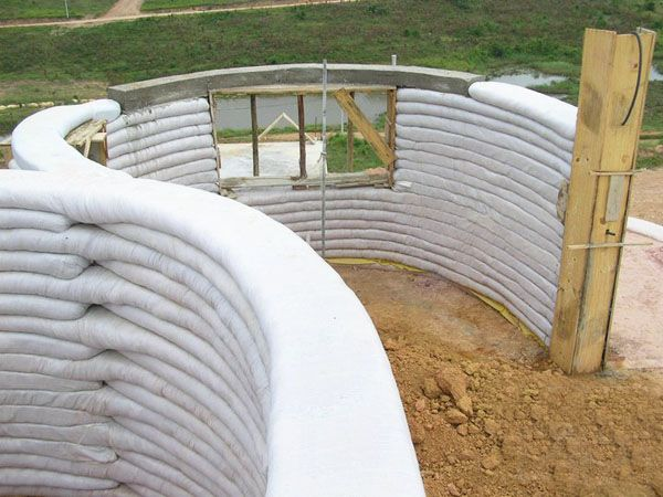 Earthbag Building, Brazil. Builder: Gabriel Raia Carneiro. Earthbag construction takes things a little further. It is based on military bunker & temporary dike building techniques. The bags are filled with clay, sand & aggregate & tamped to create cohesion. Bags are coursed like brickwork. Walls can be curved, straight, domed or topped with conventional roofs. Curved walls provide good lateral stability & straight walls longer than 5m need to be buttressed.
