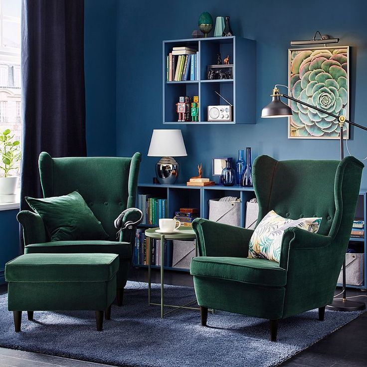 Two dark green wing-back armchairs in the corner of a dark blue living room.