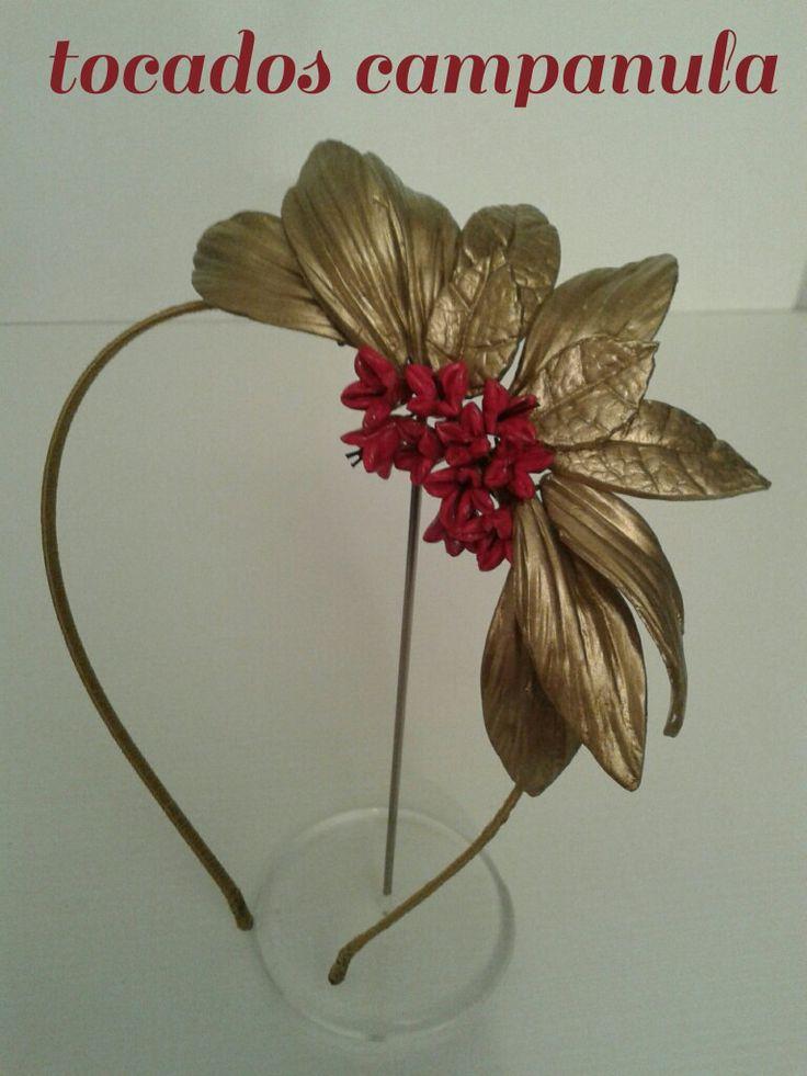 Diadema con hojas doradas y campanillas rojas.