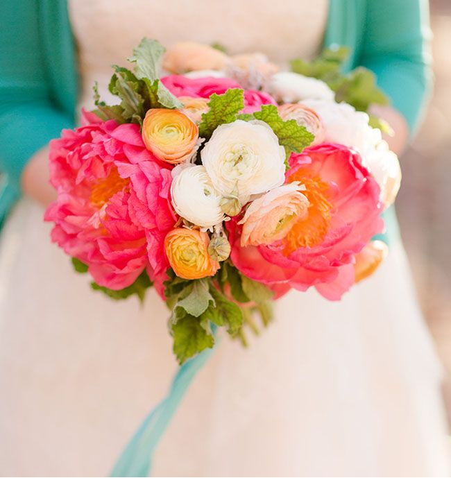 The gorgeous bouquet by Janie Medley Flora Designcontains:coral peonies, peach and white ranunculus, dusty miller and scented geranium leaves that she wrapped with midori ribbon.