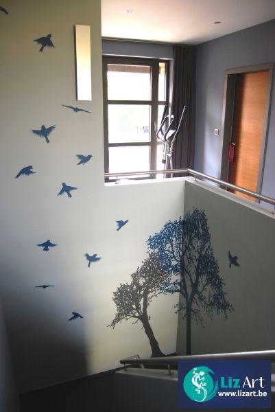 Decoratieve muurschildering van bomen in de traphal