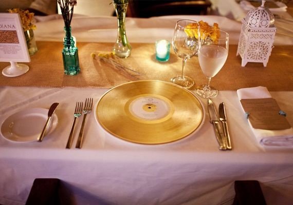 """Since they met over their love of DJing, they spray painted gold vinyl records and created custom """"record labels"""" using printable CD labels. Each record had a personal song dedication for that guest – so when they heard the song, they knew it was for them."""