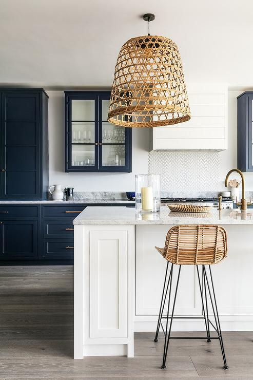 Gorgeous woven basket light pendant over white marble countertop island will sure make you glance twice. It compliments iron and wicker counter stools at white shaker cabinet island amongst surrounding blue shaker cabinetry with antique brass pulls. By Lisette Voute Design