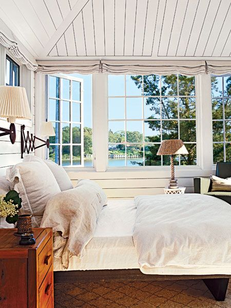 A new addition to a charming old harbor-view cottage copied the house's paneling that covers the vaulted ceiling in the master bedroom. Linen blinds retract to maximize the splendid views. (Photo: Tria Giovan)