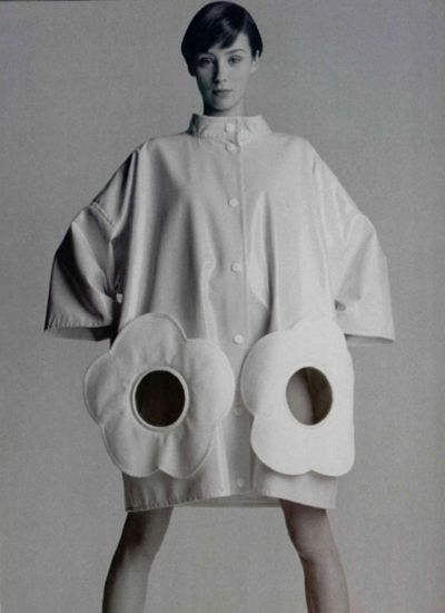 Andre courreges 1960s. using a lose fit jacket that does not highlight the silloheutte, along with flower portholes to support the space era. uses 3/4 sleeve length in a flaring apperance