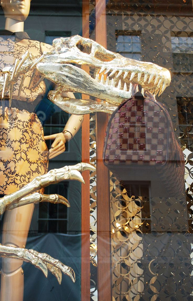 Louis Vuitton, gold cladded dinosaur skeletons interact with the mannequins and playful product placement