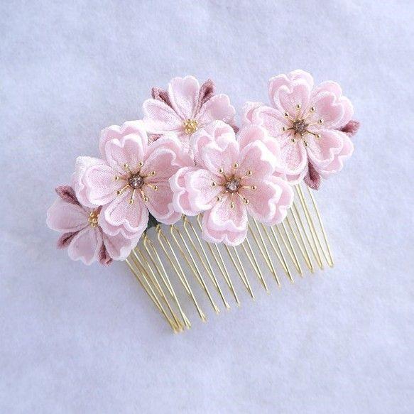 ☆受注制作になります☆ご入金から4~5日ほど頂戴致しますことをご了承いただいたうえで、ご注文いただきますようお願い致します。お急ぎの方はご注文の前にメッセージにてお問合せくださいませ。つまみ細工の桜のコームです。かわいらしい桜貝色の桜の花を大小5輪あしらって華やかに仕上がりました。アクセントとしてがくはローズがかった桜色を使用していますので大人っぽい印象です。花芯にはローズピンクのスワロフスキーがキラキ�%A