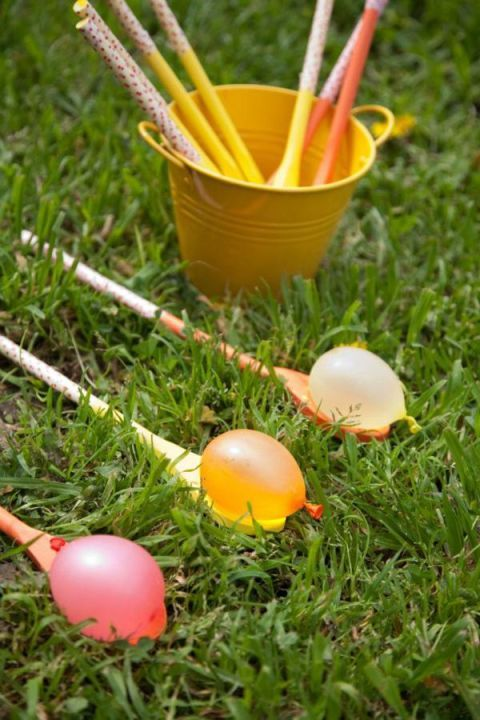 """Water Egg on a Spoon – Forget that egg on a stick race (yuck, all that yoke to clean up!). Opt instead for """"egg"""" water balloons when organizing this Easter's team races. All the fun, none of the mess. Let's be honest — you're the true winner. Click through to see the whole gallery and for more easter games."""