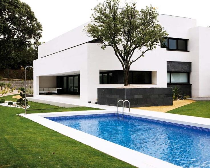La casa está recubierta de caliza y pizarra negra, en contraste con el gresite que cubre la piscina. El proyecto del paisajismo respetó la encina rodeándola de un muro de pizarra a juego con la fachada.
