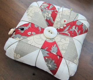 tiny half-square triangles make a pretty pattern for a quilt square pin cushion.