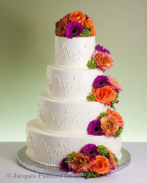 Wedding Cake- four circle tiers with white icing and white stencil work - each tier has a small group of orange and purple roses that are also on the top tier of the cake