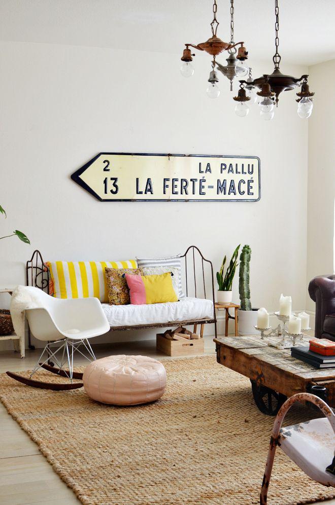 white walls, chandeliers, sofa, pouf