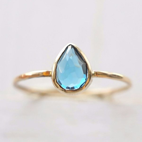 This ring made from solid 14k Gold features a pretty pear-shaped London Blue Topaz sitting atop the ring band. The 7x5mm pear shaped gem has a deep blue hue and its' color-play is a gorgeous and uniqu