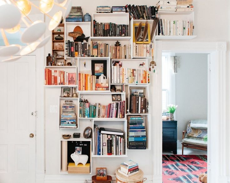 Reuse old dresser drawers to create a bookshelf installation like Mike and Kate's! The couple found free dressers on Craigslist and used the drawers to transform an empty wall in their Chicago home. #diy #decor