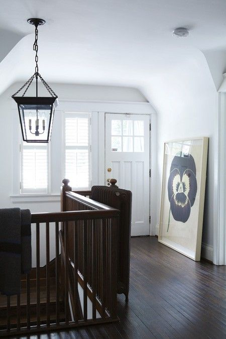 Minimalist Hallway   Let good architectural bones, like a dark wood railing and white sloped walls, inspire your decorating.   A coach lantern light adds a touch of country to the colonial dark wood floors and staircase railing, contrasting with the crisp white walls. A black radiator serves as another decorative element, balanced by a large floral art print casually leaning against the wall.