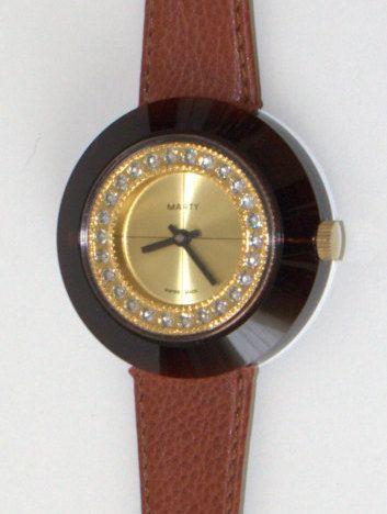 Elegante reloj de señora de la marca MARTY de los años 70. La caja de plástico semitraslúcido marrón permite ver el movimiento interior. Reloj de
