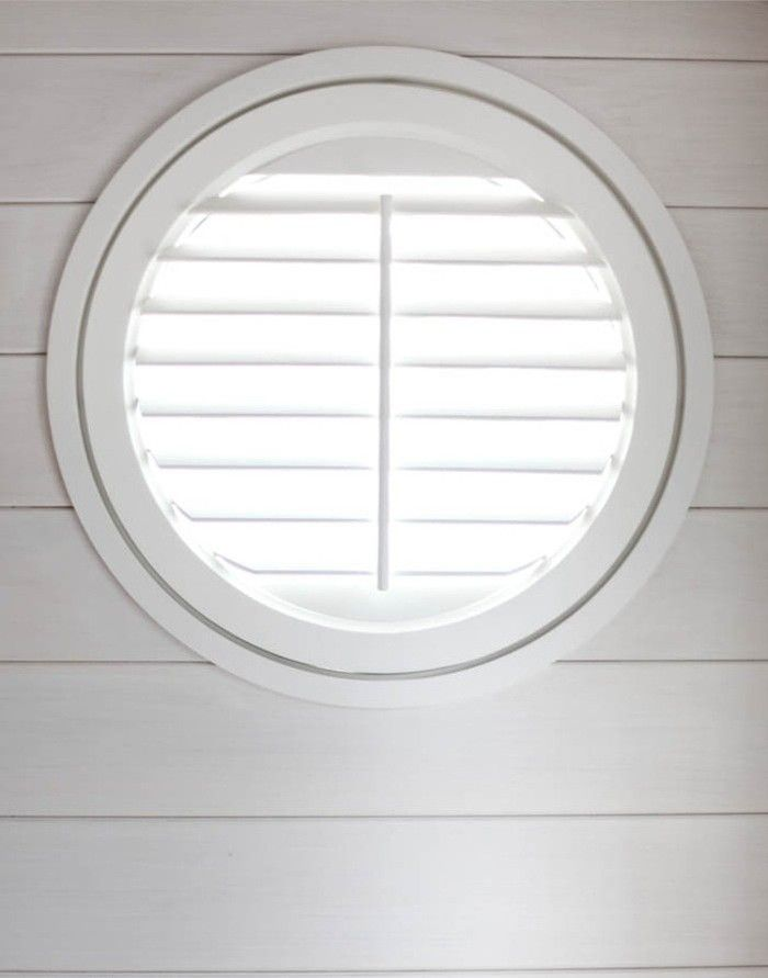 A shutter-filled porthole window set into the horizontally slatted paneling made from cypress wood with a light wash of white paint.