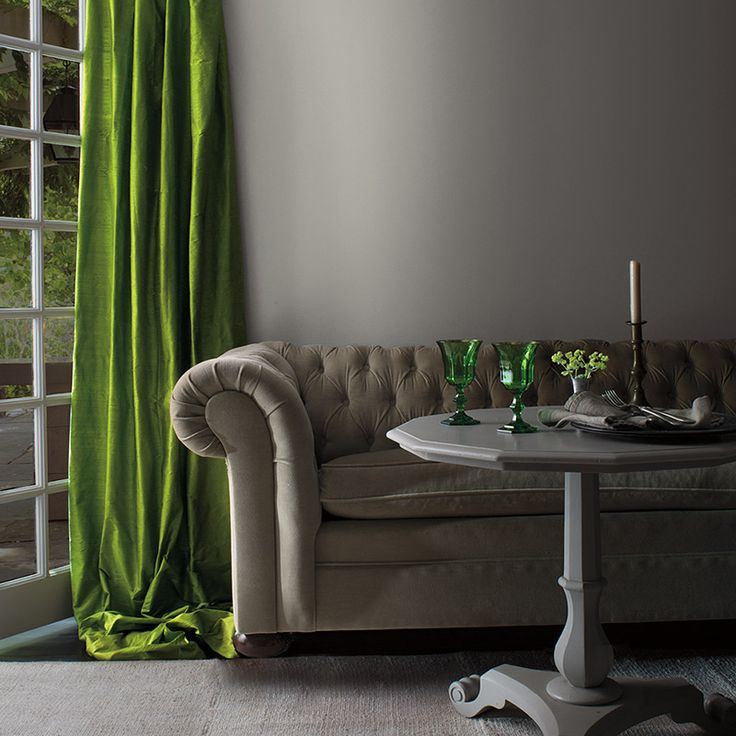 Iridescent green sparks interest in a softly elegant gray parlor with a cozy velvet couch.