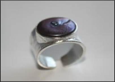 Anillo de plata con acabado martelé. En el centro hay una boca con una perla lila en su interior.  $69. Precio indicado en euros.