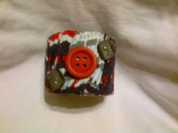 This bracelet is made with recycled t shirt material, buttons and a heavy cardboard ring from a roll of crochet cotton.