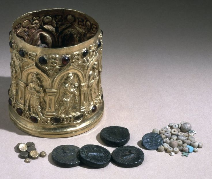 Reliquary casket, cylindrical in shape; made of gold and inset with garnets. The casket tapers slightly towards the rim and lacks a lid. The arcading round the side consists of eight pointed caitya-arches resting on pilasters. Each arch has a plain recessed face and the pilaster capitals consist of a plain fillet above a torus and a fillet. The pilaster shafts have each a recessed oblong panel with an outlined border curved at the top and the base mouldings repeat those of the capitals in a