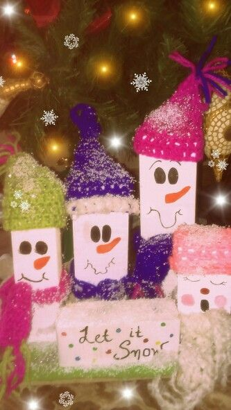DIY Christmas decoration. Cute snowmen made out of wood. They're wearing hand-knitted scarves and caps of wool.