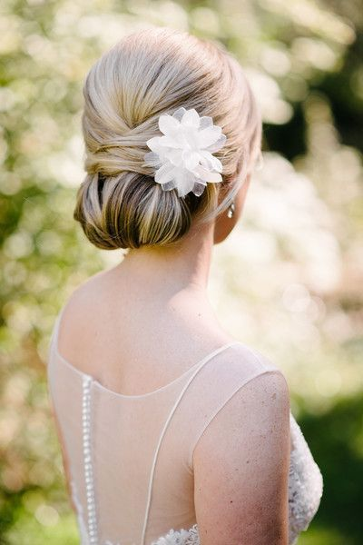 This bride wore her hair in a classic chignon, adorned with a fabric flower.