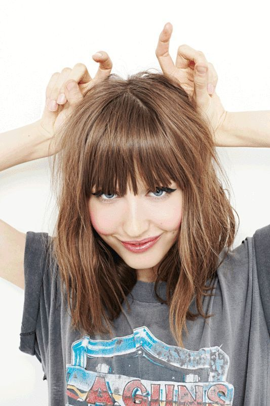 Looking for medium length hairstyles? Here are 25 you'll want to copy right now. I love her blunt bangs and slight wave in her hair.