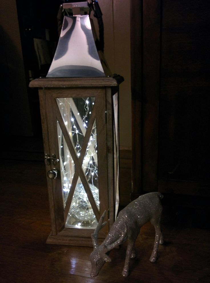 Fairy string lights in a wooden lantern. Pretty year round! For a woodland rustic Christmas / winter look simply add a glitter deer! I hid the battery pack by taping it up inside the metal top.
