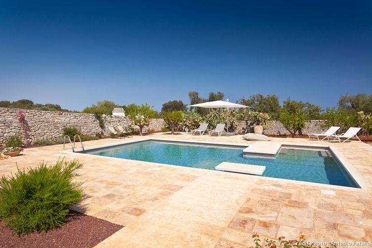 Masseria Grottone, un gîte rural d'exception en Italie : au bord de la piscine, les transats de la marque Emu sont disposés pour prendre le soleil.
