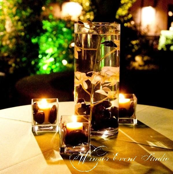 Centerpieces Of Submerged Orchids With Black River Rocks And Beta Fish Surrounded By Votives In