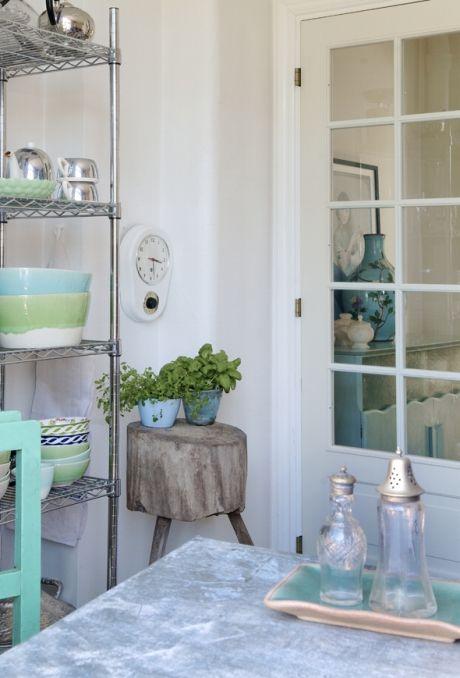 ᏋᏆ ℒᏋᏉᏋᏁᎠᏋ ℋᏠᏋℳ ℱᎽℒᎠᏆ ℳᏋᎠ ℱᏌᏁᎠ: Den minimalistiske stålreol i køkkenet er fyldt med grønne og turkise farver fra Rice. Ved siden af står en gammel slagterblok fra Who found Otto. Der er adgang til terrassen og den dejlige have direkte fra køkkenet. Her lader Susanne op ved at luge, plante eller slænge sig i det store gamle træbadekar, som hun har stående som en fast installation.