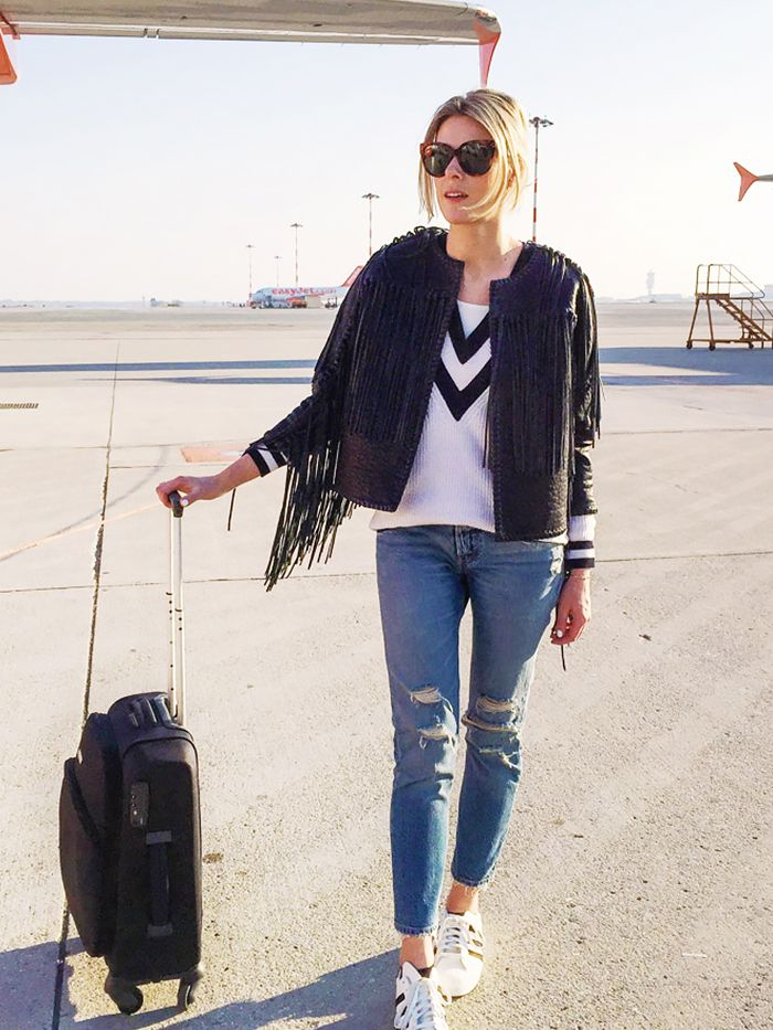 Sofie Valkiers of Fashionata wearing a black jacket with fringe, ripped jeans, and sneakers