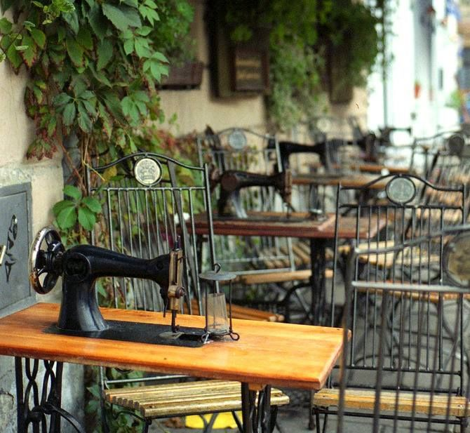 Singer Cafe, Krakow, Poland. Singer Café is a laidback hang-out of the Kazimierz cognoscenti. This relaxed café-bar's moody candlelit interior is full of character. Alternatively, sit outside and converse over a sewing machine affixed to the table.