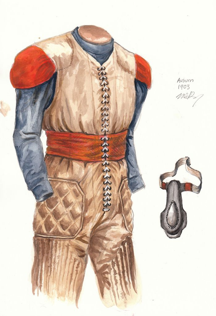 """1903 - White-tan laced canvas """"one piece jumper"""" with orange mid-section and sewn-on orange shoulder pads. No uniform number or lettering on front. Black rubber nose guard ... Coached by Billy Bates in his only year of coaching, the team went 4 and 3 and were captained by J. P. Paterson."""
