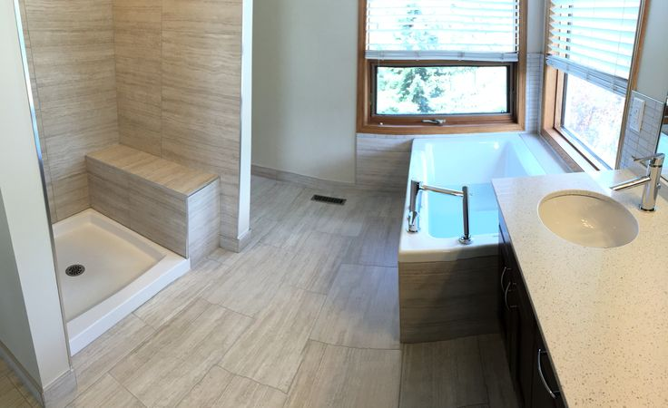 On this renovation we installed infloor heat with 24 x 12 tiles, new deep soaker tub complete with wand wash and new cabinets with quartz top.