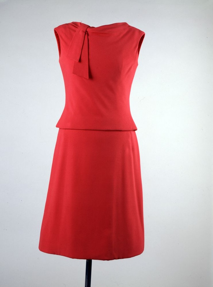 """Red Day Dress Maker: Oleg Cassini (American, b. France, 1913-2006) Date(s) of Materials: 1961 Place Made: United States Medium: Crepe Dimensions: 42"""" center back Description: A sleeveless red crepe top with matching A-line skirt. The top is collarless with an off-center tie at the left shoulder. Historical Note: This dress was worn by First Lady Jacqueline Kennedy for a luncheon at La Fortaleza, Governor Luis Muñoz Marín residence in Old San Juan, Puerto Rico during her State Visit."""