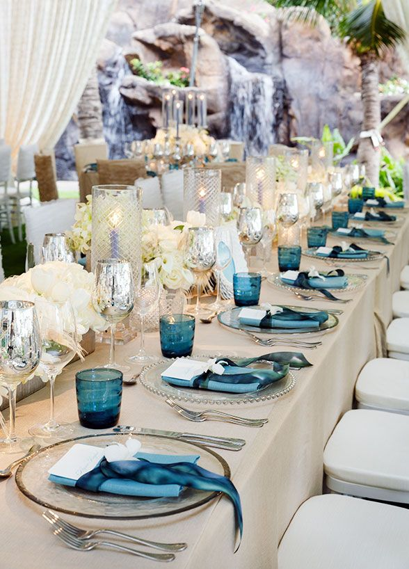 The reception was a grand tented affair, with tables covered in reflective metallic, pops of blue and lush white blooms.
