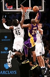 Kobe Bryant throws down a nasty dunk between Brooklyn Nets, Gerald Wallace and Kris Humphries, during the second half at Barclays Center leading to a Lakers win.
