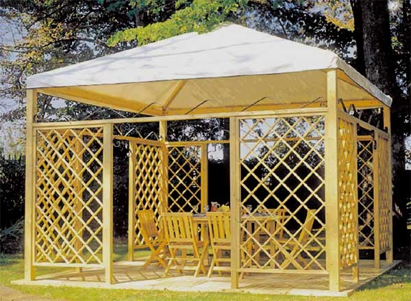 este mirador de madera con cubierta de lona blanca, la mesa y las sillas de madera estan en la terraza.