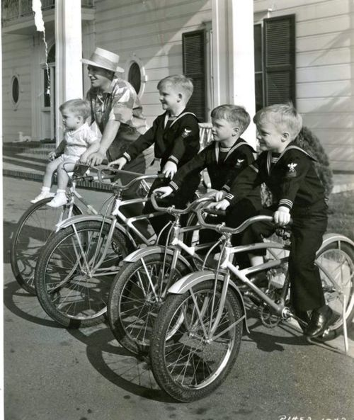 Bing and Lynn Crosby, Gary, Phillip and Dennis Crosby ride bikes.