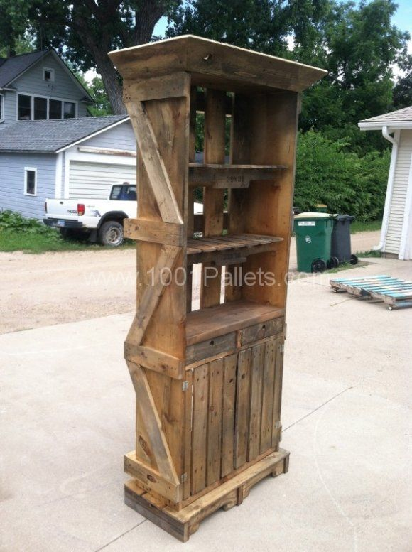 This Pallet Hutch was created by two pallets and a shipping crate. It has two drawers, doors with storage in the bottom along with a counter and two upper shelves made from pallets.