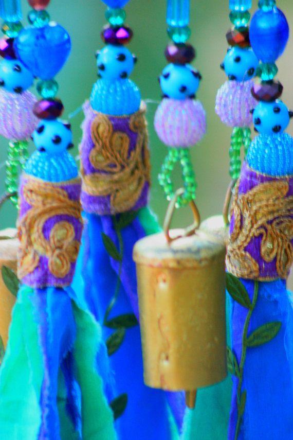 Carillón de viento púrpura y verde turquesa, cuentas móvil con campanas de bronce y borlas de tela, decoración Bohemia para el hogar o para la decoración de su patio al aire libre Me gusta el sonido de las campanas y mirando brillantes cuentas de cristal. También me encanta las borlas y fabricación de ropa reciclada y bufandas. Un día, por accidente, cuelga una borla en el mismo clavo de campanas móviles y descubrió lo maravilloso se ve cuando se combinan! Este móvil está hecho de madera…
