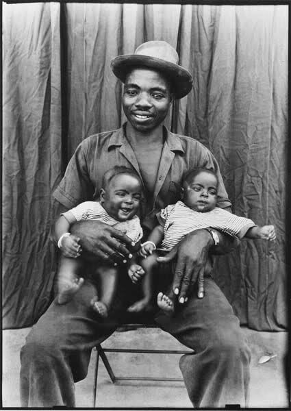 Vintage b&w photo of Black Father with his adorable twins babies. circa unknown, genders unknown.