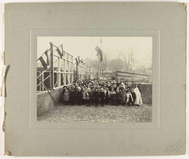 Boersma   Inzegening lagere school, Boersma, 1920 - 1930   Bij een school in aanbouw zijn katholieke geestelijken bezig de school te zegenen. Op de voorgrond een paar nonnen, daarachter kinderen. Aan de kozijnen hangen Nederlandse vlaggen.