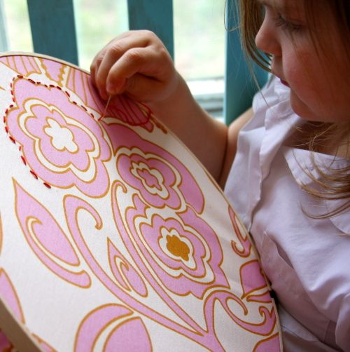 Kids embroidery. Trace bold fabric with needle and thread.