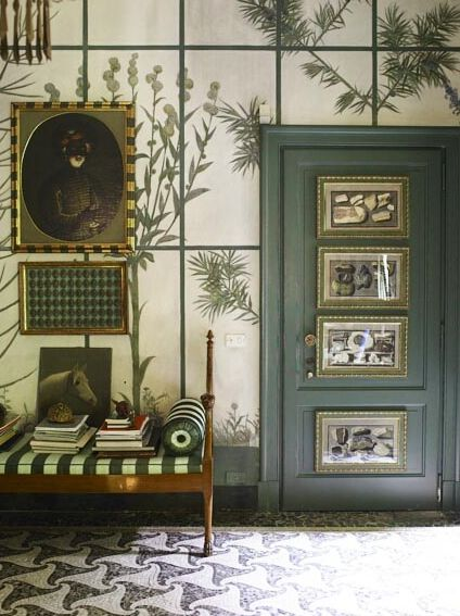 Garden room features overscale bontanical trompe l' oeil, patterned mosaic floor, green mouldings, organic illustrations, green & white striped settee cushion..