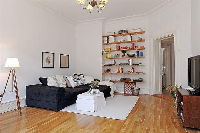 black couch bookshelves white walls